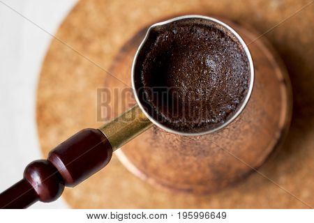 Turkish coffee close-up. Fragrant freshly brewed coffee in a copper pot