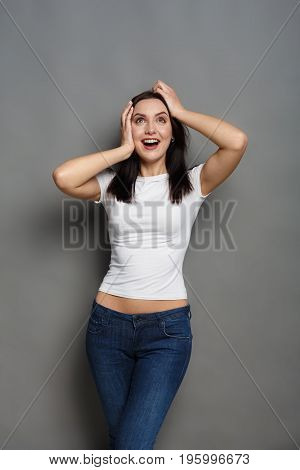 Just happy. Young smiling exited woman in casual wear holding hands on head and shouting while standing against gray studio background.