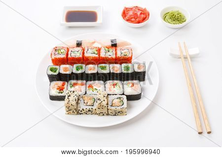 Japanese food restaurant, colorful rolls, gunkan and sushi platter. Set with chopsticks, soy sauce, ginger and wasabi on white background