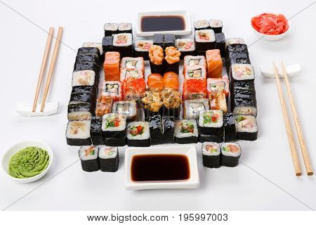 Sushi delivery. Set of rolls, unagi, gunkan served with chopsticks, soy sauce, ginger, wasabi on white background. Japanese dinner for two, pov