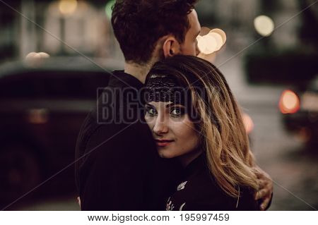 Stylish Gypsy Couple In Love Hugging In Evening City Street At Moving Car Lights. Woman And Man Embr