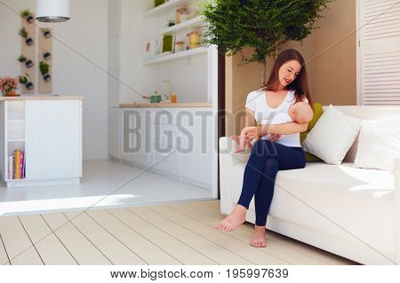 Young Mother Holding On Hands Infant Baby, While Sitting On Open Space Kitchen