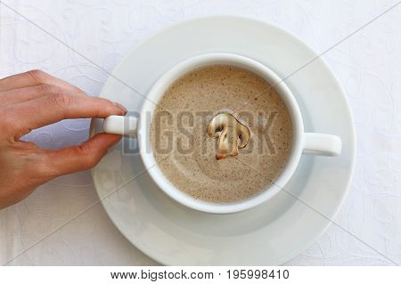 Woman Hand Holding Tureen Of Champignon Cream Soup