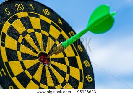 Business goals or target concept with selective focus on a dart pin in the center of dartboard with blue sky background.