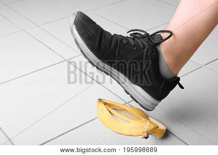 Male's leg in black trainers slips on a banana peel, on gray background. Bright yellow banana peel on the floor. Accident and risk concept.