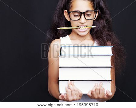 Little Girl With Glasses And Pencil Holds Books On Black Background