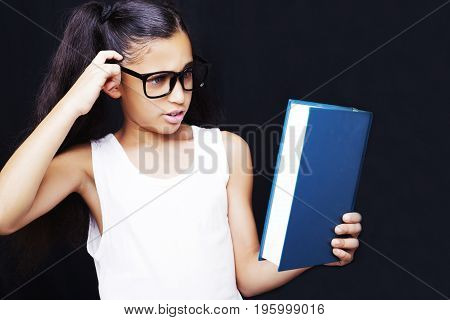 Adorable Girl Studying With Eyeglasses And Book In Hand On Dark Background