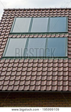 Solar panels on the roof of a building with brown tiles
