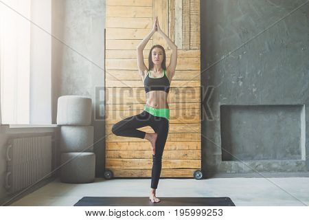 Woman in yoga class in tree pose. Fit girl balancing in vrksasana. Healthy lifestyle in fitness club, copy space on wall