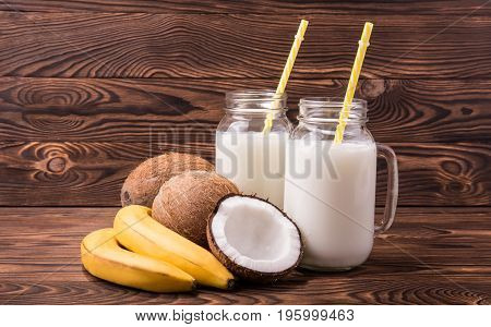 A colorful set of fruits and milk on a brown wooden background. Fresh yellow bananas near transparent mason jars filled with fresh coco milk. Glasses with straight yellow straw on the desk.