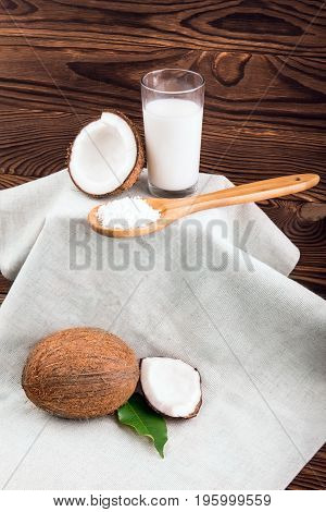 A glass full of fresh coconut milk and wooden spoon with coconut chips on a light fabric and on a dark wooden background. Whole and cut in half cocos with green leaves.