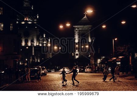 Lovers Running Through Empty Road In The Evening City Street. Stylish Couple In Love Having Fun And