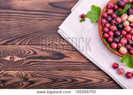 Juicy, ripe and nutritious multi-colored gooseberries with fresh leaves in a wooden crate on a dark brown background. A bright brown basket with nutritious gooseberries on a gray bag.