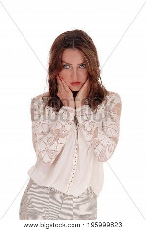 A beautiful young woman in a lace blouse and brunette hair standing looking serious with her hands on face isolated for white background.