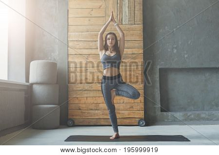 Woman in yoga class making asana exercises. Girl do tree pose, vrksasana. Healthy lifestyle in fitness club. Stretching