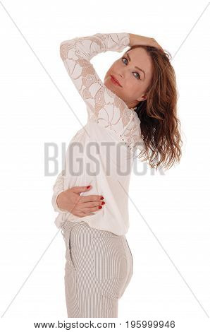 A young beautiful woman standing in a lace blouse and trousers with on hand on her head in profile isolated for white background.