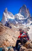 Male trekker resting on the rock in front of the stunning and impressive Mount Fitz Roy near El Chalten in Patagonia, Argentina poster