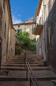 View of alley with houses, staircase and handrail at sunset, in the lovely village of Grйoux-les-Bains. Located in Alpes-de-Haute-Provence department, Provence region, southeastern France poster