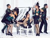 The studio shot of group of dancers dancing at retro costumes. Concept of cabaret, luxury party and jazz poster