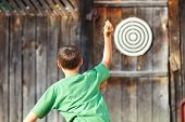 Young boy in green t-shirt playing darts outdoor poster