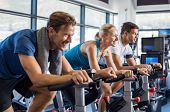 Group of smiling friends at gym exercising on stationary bike. Happy cheerful athletes training on exercise bike. Young men and woman working out at a class in the gym. poster