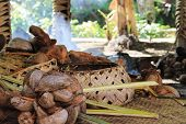 A traditional Samoan cooking area inside a hut with woven baskets and coconuts ready to prepare. poster