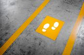 Walkway lane in parking building. Painted yellow footsteps between parallel yellow lines on abstract cement floor. Step by step concept. poster