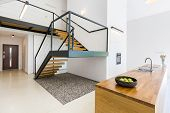 Modernistic interior with massive staircase of black metal and wood and space filled with pebbles underneath poster