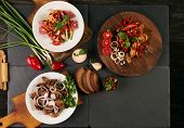 Set of three bowls with different dishes: fried mushrooms fresh low-calories salad with vegetables and grilled chicken breast. Fresh dietary rye bread and branded sauce on dark stone background poster