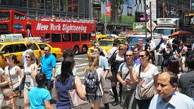 NEW YORK, NEW YORK - July 2, 2014: New York City Street Scene. Everyday people crossing a busy intersection in New York City.