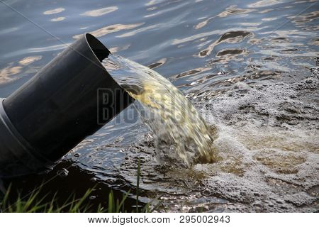 Water Pumping Pipe In A Ditch Between Fields Full Of Tulips In Noordwijkerhout