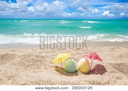 Happy Easter Background With Eggs And Coctail Umbrellas On The Sandy Beach Near Ocean.