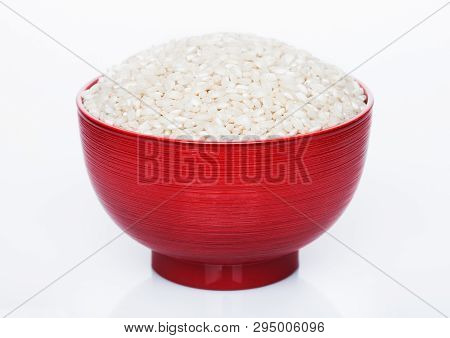 Red Bowl Of Raw Organic Arborio Risotto Rice On White Background.
