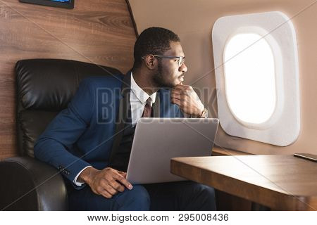 Attractive And Successful African American Businessman With Glasses Working On A Laptop While Sittin