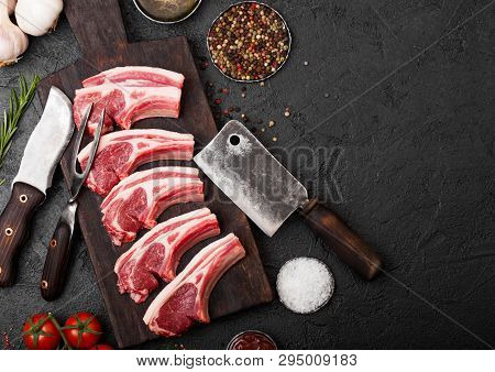 Fresh Raw Butchers Lamb Beef Cutlets On Stone Board With Vintage Meat Fork And Knife And Hatchet On
