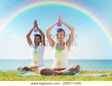 mindfulness, spirituality and outdoor yoga - couple meditating in lotus pose with seven chakra symbols over sea and rainbow background