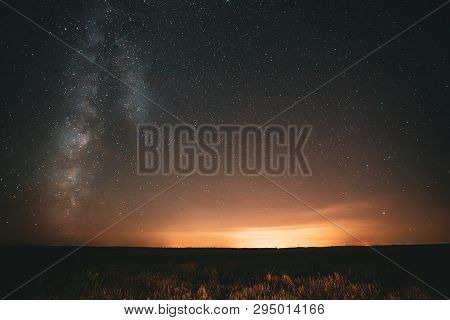 Natural Night Sky Stars With Milky Way Galaxy Above Field Landscape. Real Photo Starry Sky After Sun