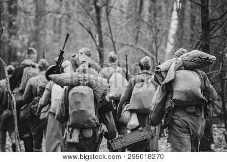Re-enactors Dressed As World War Ii Russian Soviet Red Army Soldiers Marching Through Forest In Autu