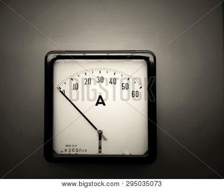 monochrome square industrial ammeter with an analogue dial with numbers with standard electrical symbols on a white dial on a grey background poster