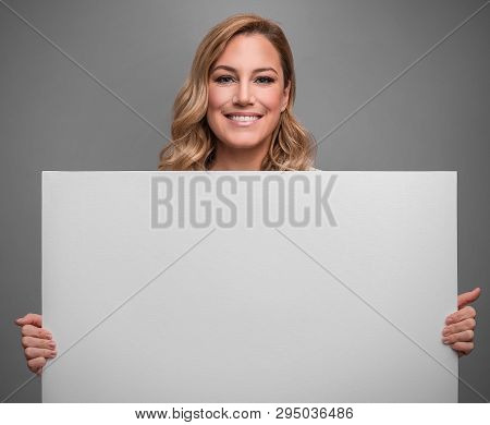 Attractive Blonde Holds White Blank Empty Poster For Your Text Or Image On Gray Background.