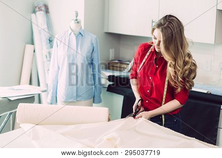 Happy tailor woman cut piece fabric working in  atelier studio poster