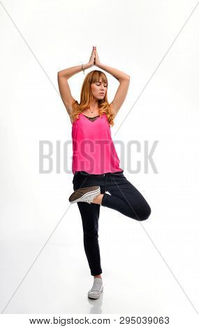 Full Length Portrait Of A Young Red-haired Fitness Model In Pink Sportswear Doing Yoga Or Pilates Ex