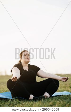 Body Positive, Yoga, Meditation, Tranquility, Relax. Overweight Woman Meditating Sitting At Yoga Mat