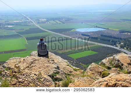 Lonely Man Sits On The Edge Of A Cliff And Looks At The Magnificent Landscape Of The Jezreel Valley,