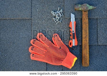 Close Up View On Bitumen Asphalt Shingles On A Roof  With Hammer,nails And Stationery Knife. Use Of