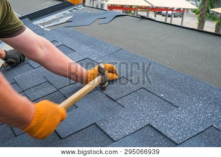 Workers Hands Installing Bitumen Roof Shingles Using Hammer In Nails.