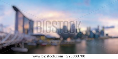 Out Of Focus Of Colorful Singapore Business District Skyline After Sun Set At Marina Bay.