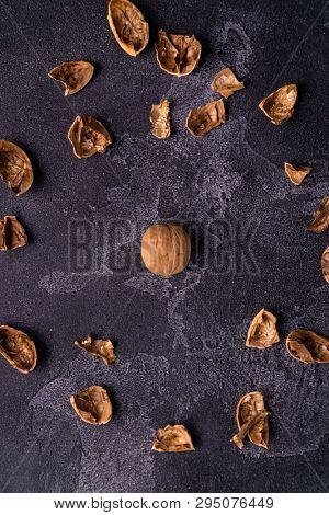 Cracked walnut shell scattered across the dark slate table. Healthy nuts and seeds composition, background.