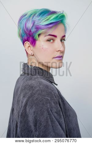 A Young Woman With Short Hair, A Pixie Bob Haircut, Different Colored Hair, Blue, Green, Violet.