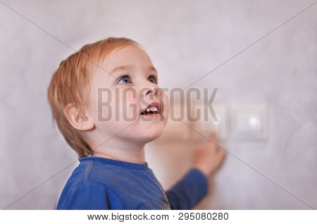 Pretty Blonde Caucasian Baby Boy Turns On/off The Light-switch, Looking Up. Big Blue Eyes, Close Up